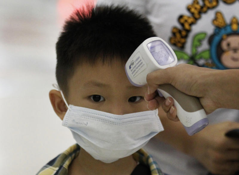 FILE PHOTO: A boy gets his body temperature checked by a Thai officer upon his arrival at Suvarnabhumi Airport in Bangkok on June 19, 2015 after Thailand confirmed its first known case of the deadly MERS virus. (AFP)