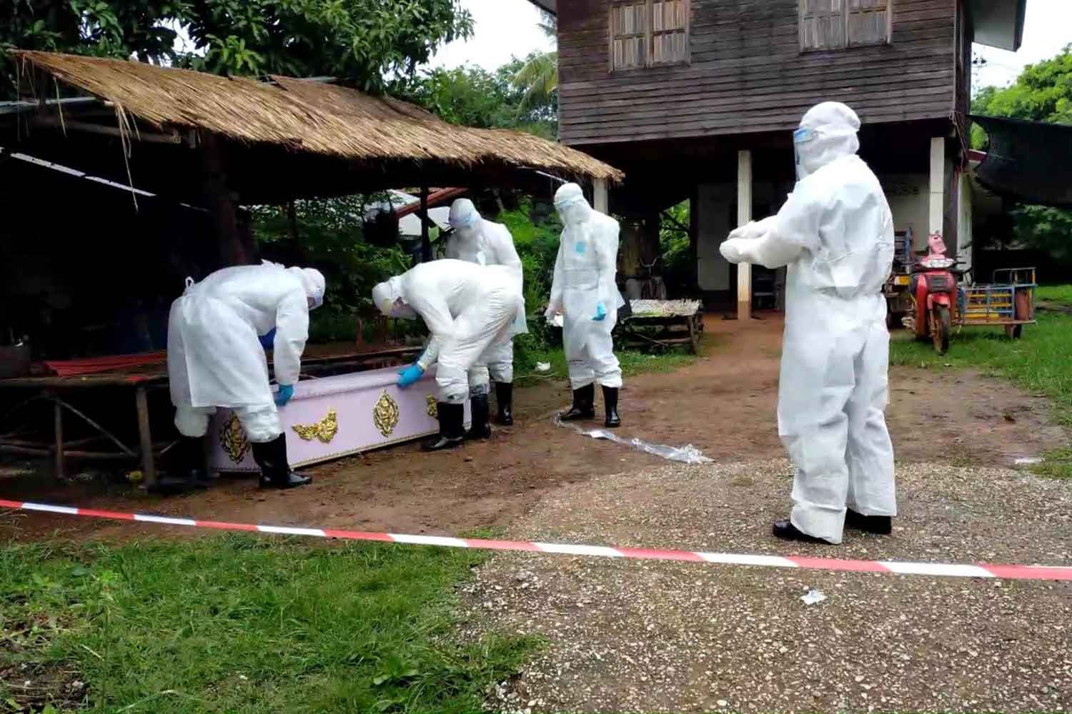 Medical staff in PPE suits from Hong Han Hospital in Udon Thani province place the body of the Lao man who died on Tuesday from an unknown cause in a coffin. A laboratory test will determine whether he died of Covid-19. (Photo: Yuttapong Kumnodnae)