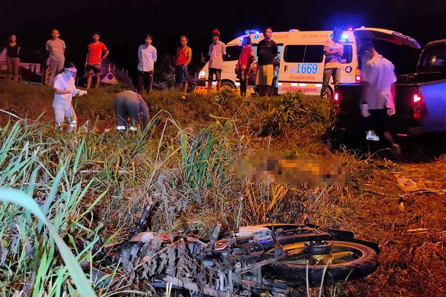 Police and rescue workers at the scene of the crash between a motorcycle and pickup truck on Mancha Khiri-Phra Yuen road in Mancha Khiri district, Khon Kaen province, early Wednesday. Two men on the motorcycle were killed. (Photo: Chakrapan Nathanri)