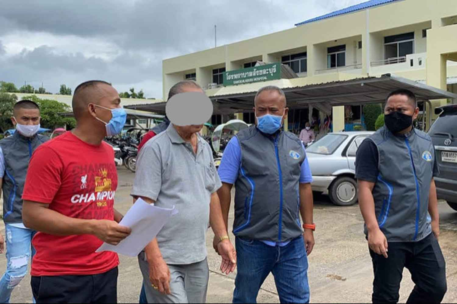 Sakol Wichaidit, second left, is escorted to Muang police station in Surat Thani. He was arrested in Sangkhlaburi district, Kanchanaburi, after 12 years on the run. (Photo: Supapong Chaolan)