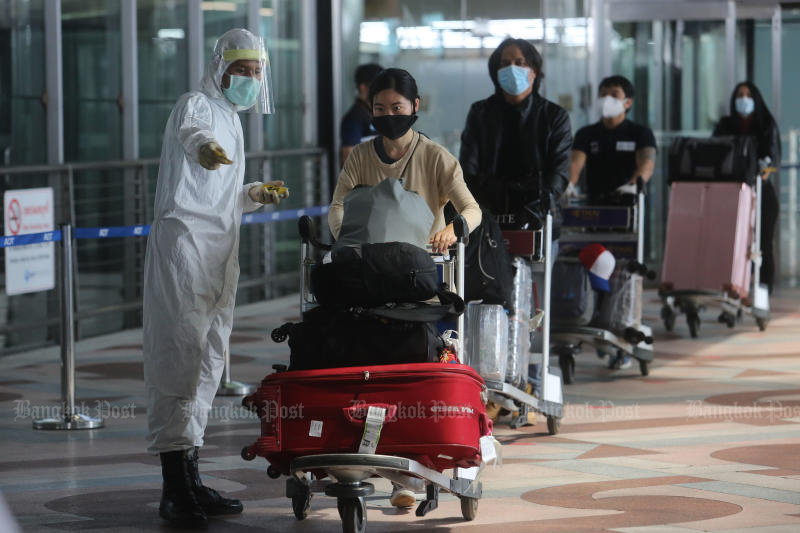 Returnees are directed to an exit at Suvarnabhumi airport to board a bus to alternative state quarantine facilities on Friday. Thailand found two new cases who completed quarantine at state facilities, officials said on Wednesday. (Photo by Wichan Charoenkiatpakul)