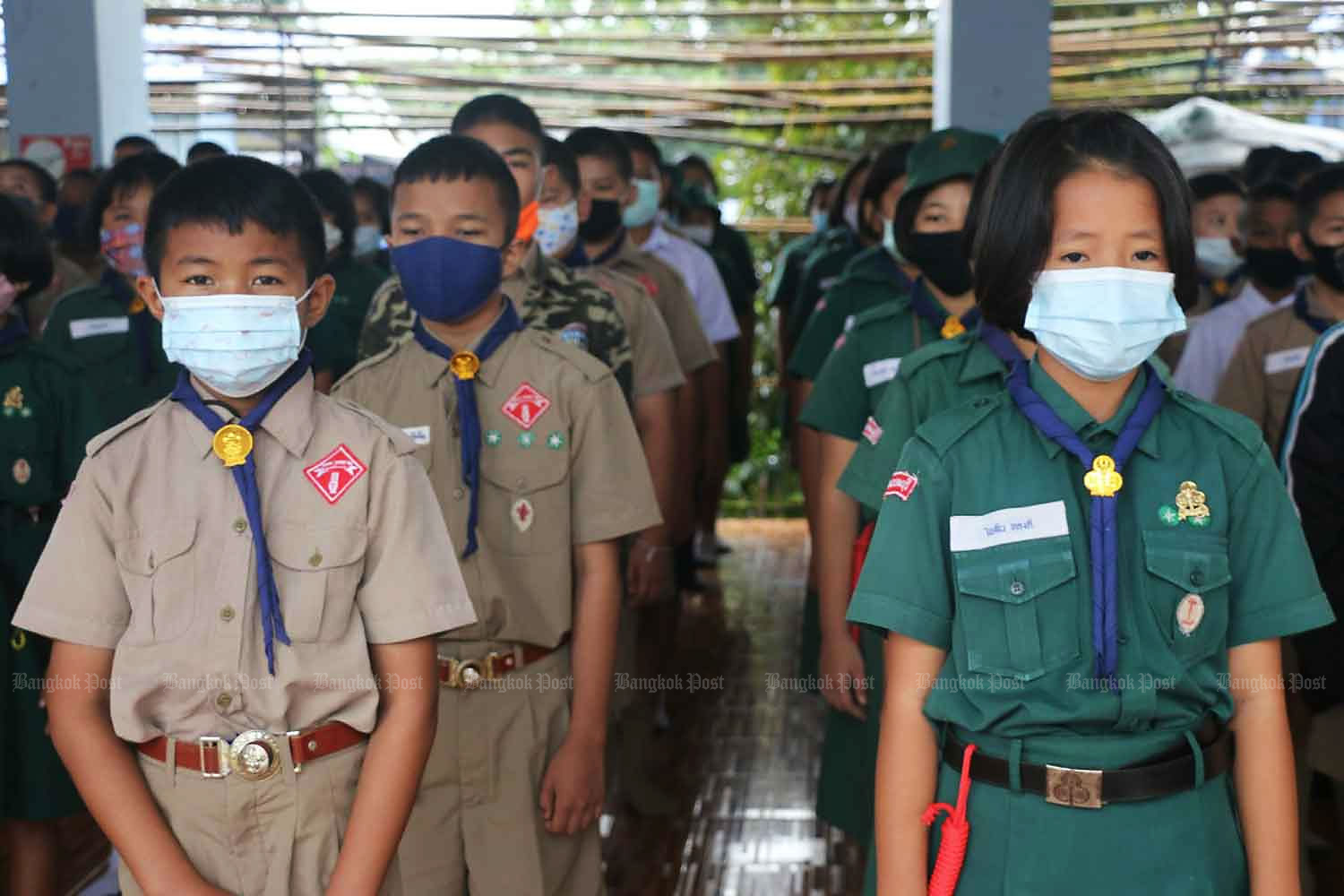 Students at Anuban Sangkhla Buri School in Kanchanaburi's Sangkhla Buri district gather at assembly on Wednesday. The school in this border district next to Myanmar imposes strict measures to curb the Covid-19 pandemic. (Photo by Piyarat Chongcharoen)