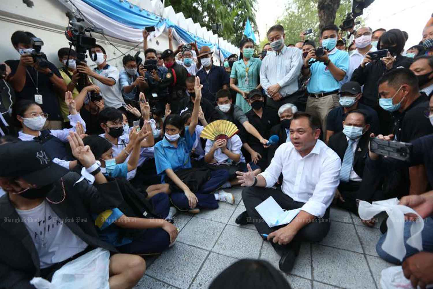 Education Minister Nataphol Teepsuwan on Wednesday sits down in front of his ministry to meet 500 students who called for a new constitution, House dissolution and an end to government harassment. (Photo by Pattarapong Chatpattarasill)