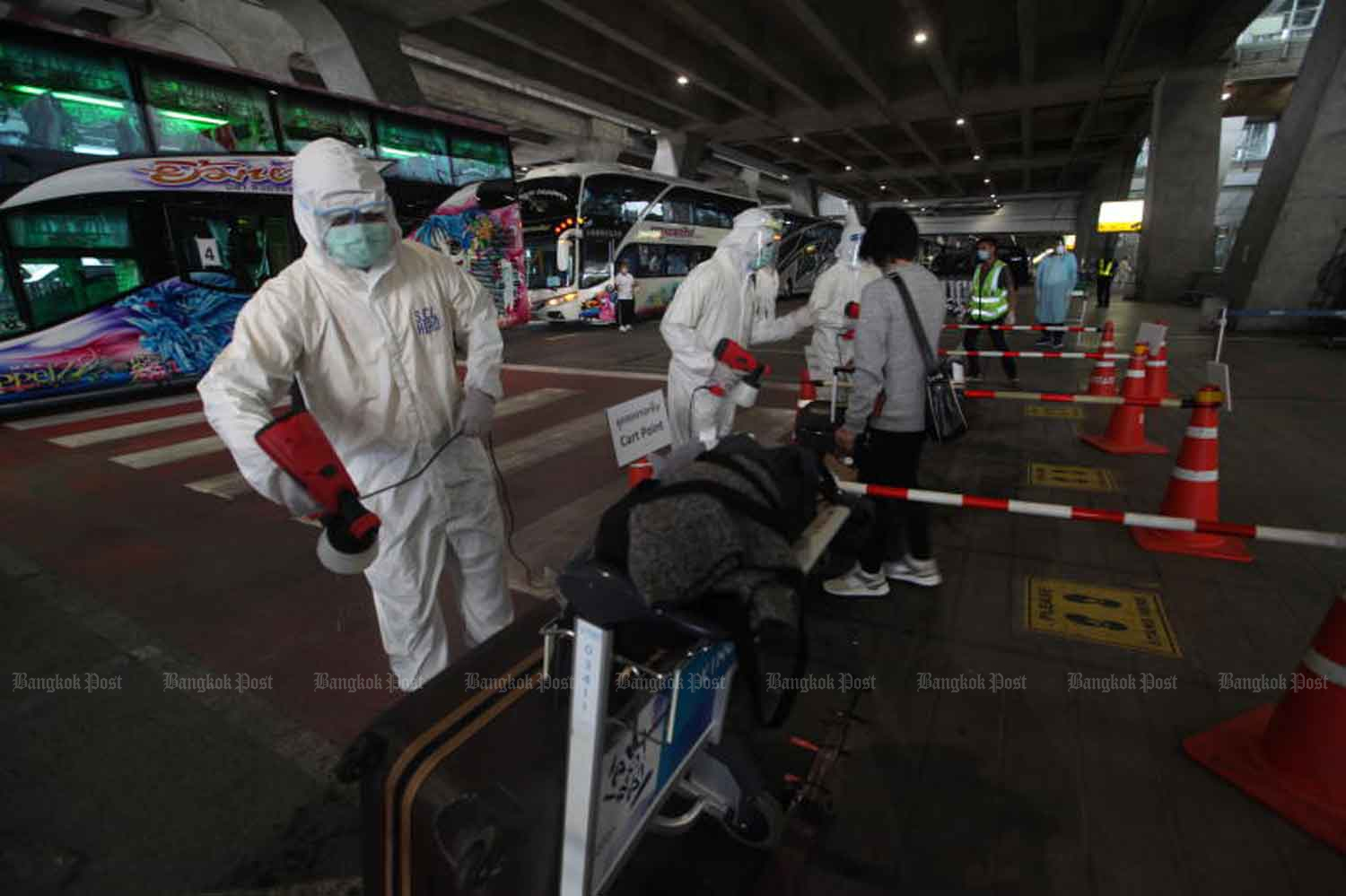 Disease control officials disinfect returnees and their luggage before they are taken to to quarantine, at Suvarnabhumi airport in Samut Prakan province. (File photo: Arnun Chonmahatrakool)