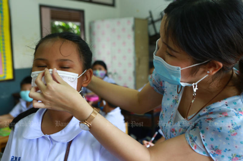 A teacher helps fit a mask to a pupil's face at Intarumphun Anusorn School in Muang district of Samut Prakan, part of the school's anti-Covid-19 measures. (Photo: Somchai Poomlard)