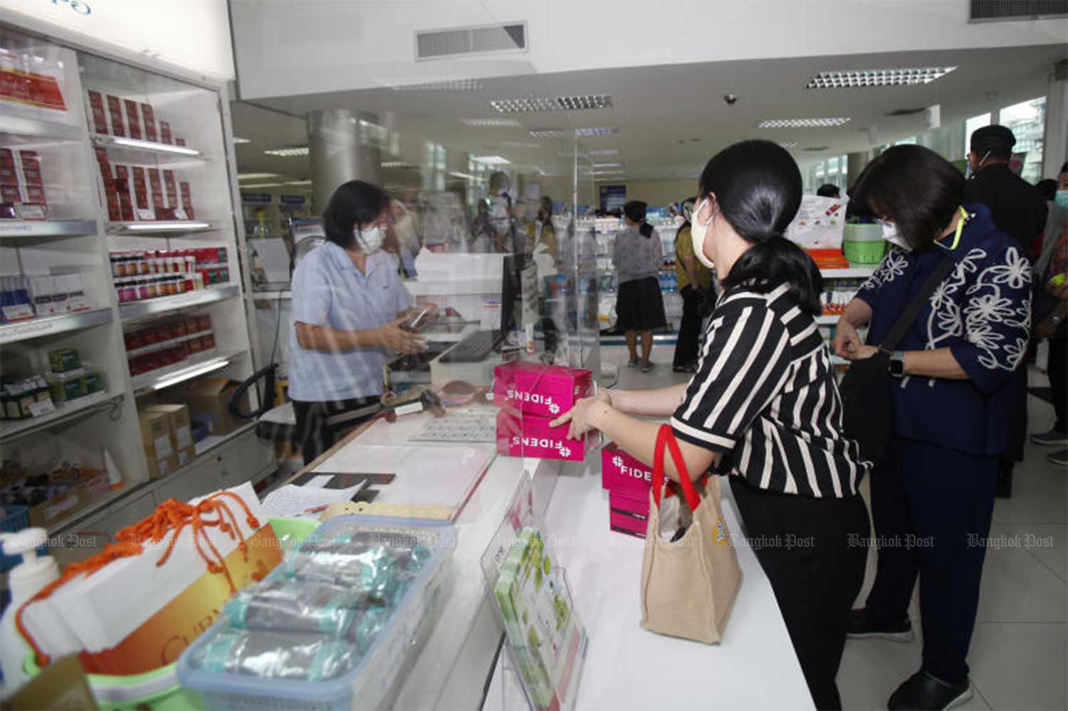 People queue to buy surgical masks at the Government Pharmaceutical Organisation's Ratchathewi branch in Bangkok on Thursday. Each box, containing 50 masks, costs 125 baht with no purchase limits. (Photo by Nutthawat Wicheanbut)