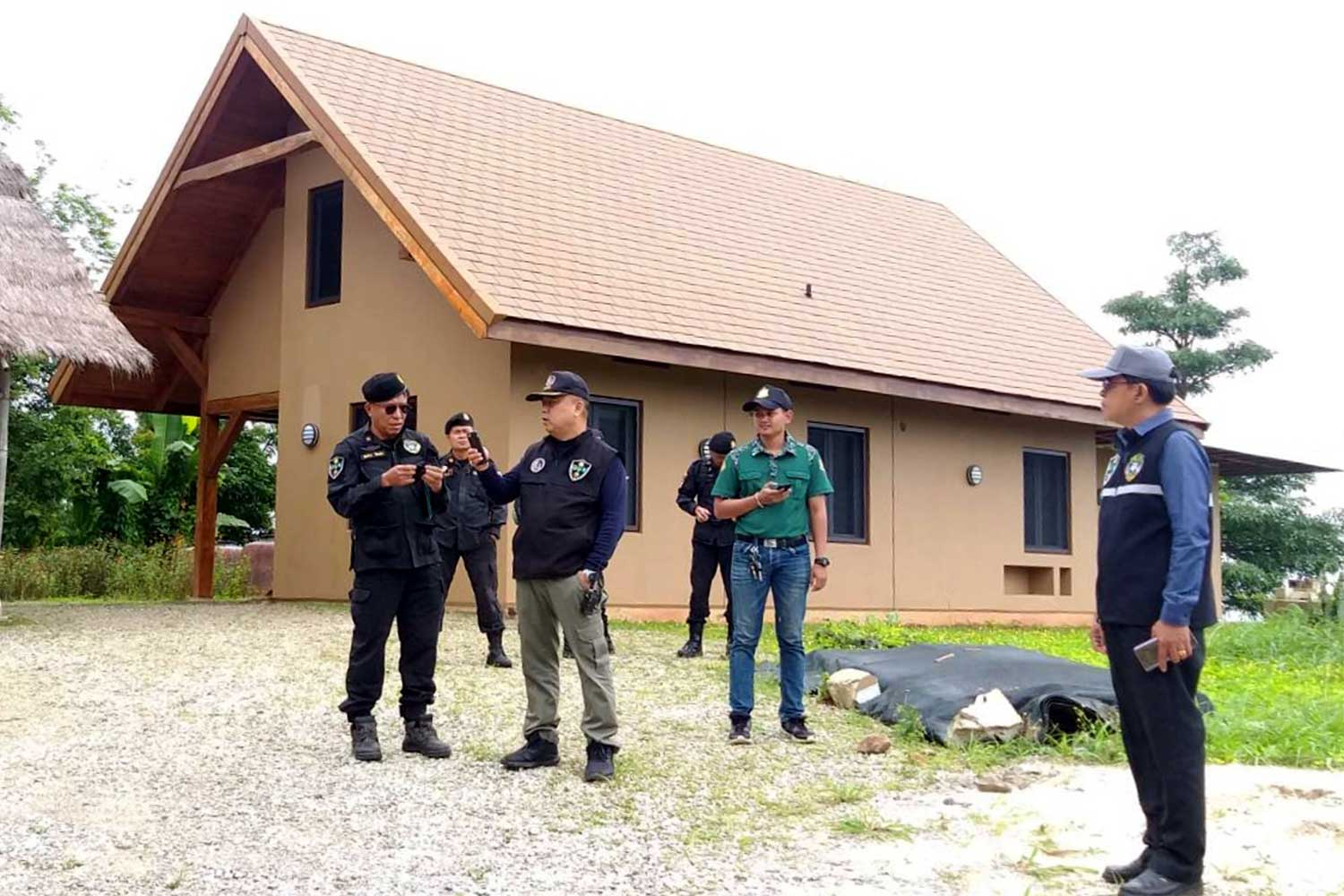 Officials inspect the site of a house near Khao Kho national park in Phetchabun. A senior government official reportedly owned the land plot and allowed her American friend to build a house there. (Photo: Sunthorn Kongwarakom)