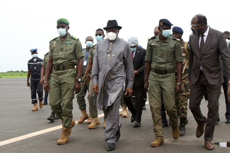 Ex-Nigerian President Goodluck Jonathan, wearing a hat, at Bamako's airport alongside the junta's second-in-command Colonel Malick Diaw, left