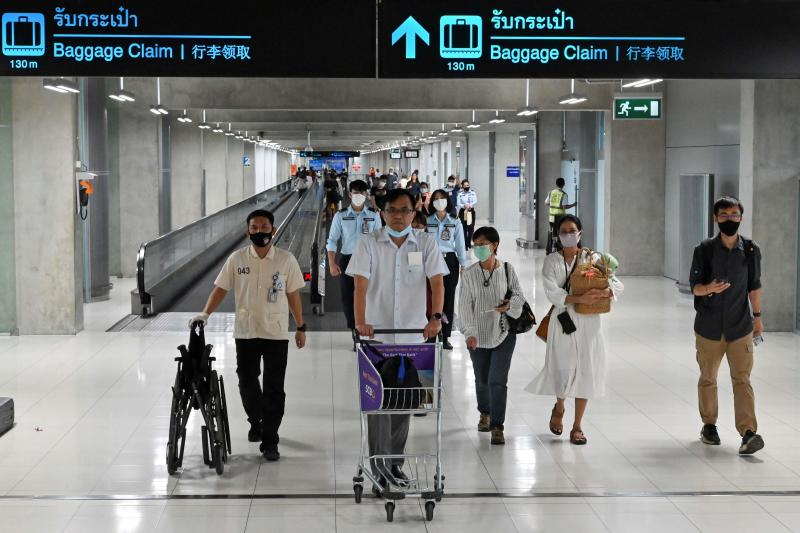 Passengers wearing face masks as a preventive measure against the Covid-19 coronavirus walk along a concourse at the departure area of Suvarnabhumi airport on Friday. (AFP photo)