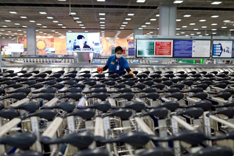 An airport staff member wears a protective mask due to the coronavirus outbreak as she sanitises rows of luggage carts at Suvarnabhumi Airport on March 12, 2020. (Reuters photo)