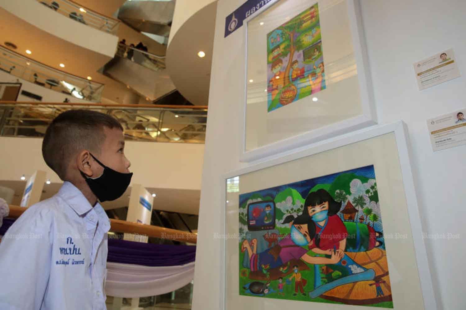 A school pupil views an exhibition of children's paintings about their Covid-19 experience, at the Bangkok Art and Culture Centre on Tuesday. (Photo: Chanat Katanyu)