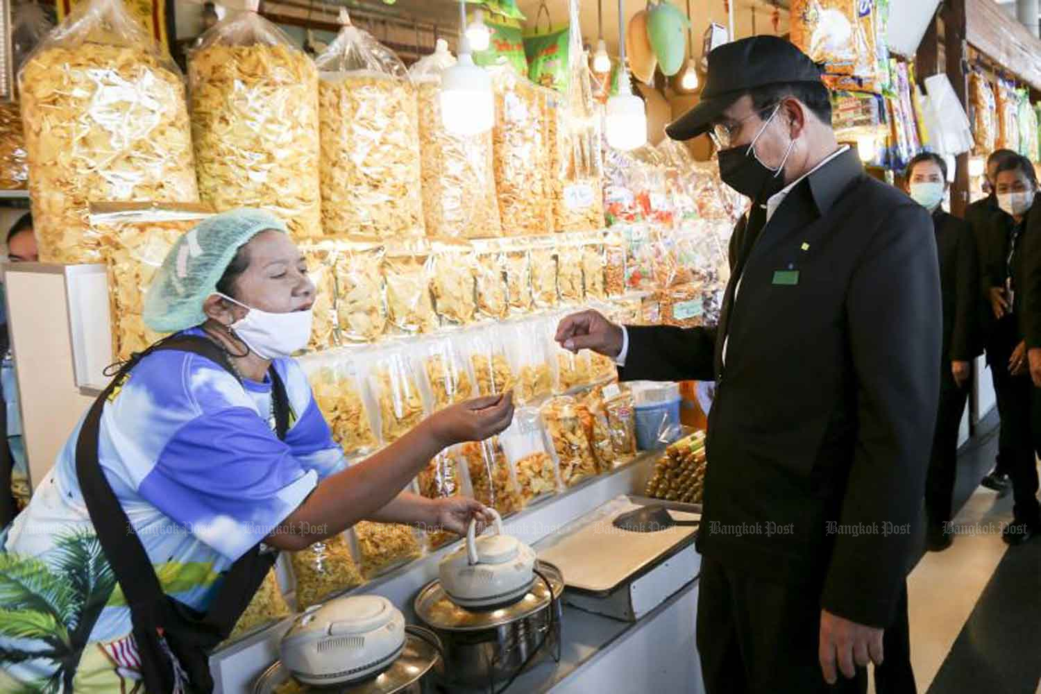 Prime Minister Prayut Chan-o-cha tries durian chips during his visit to Rayong province on Tuesday. He said the country needed to welcome back foreign tourists, for the survival of its economy. (Photo: Pattarapong Chatpattarasill)