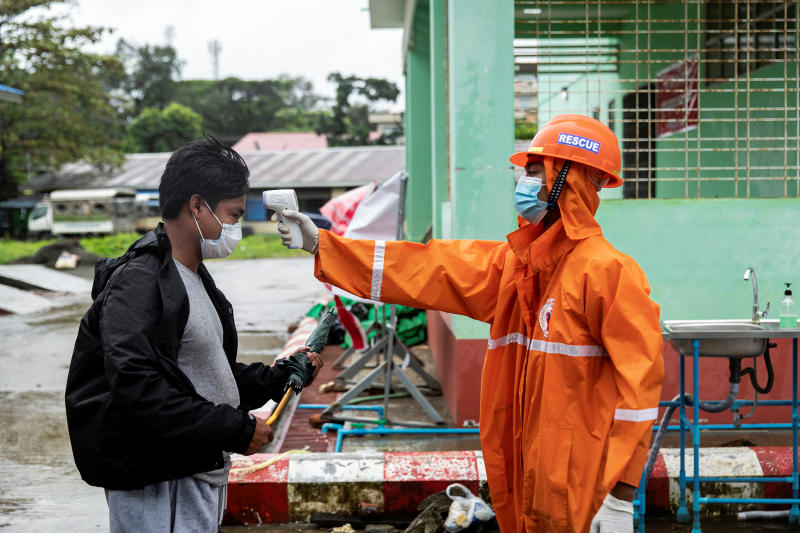 A volunteer checks the temperature of a man at the entrance of Sittwe Hospital, amid the outbreak of the coronavirus disease, in Sittwe, Rakhine State, Myanmar on Monday. (Reuters photo)