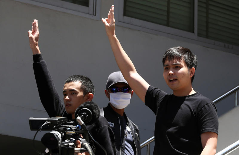 Pro-democracy leaders Tattep Ruangprapaikitseree and Panumas Singprom flash the three-fingers salute as they are escorted by police officers after being arrested, at a police station in Bangkok, on Wednesday. (Reuters photo)
