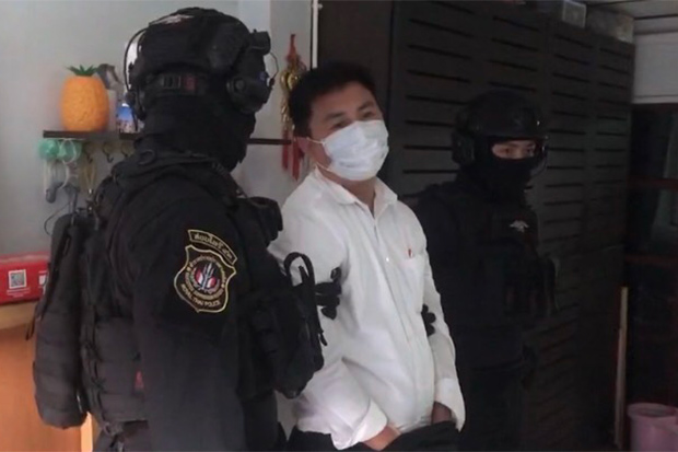 Narcotics Suppression Bureau police keep a close watch on Penthai Khamhom during the search of his house in Huai Khwang, after his arrest on Thursday. (Photo: Wassayos Ngamkham)