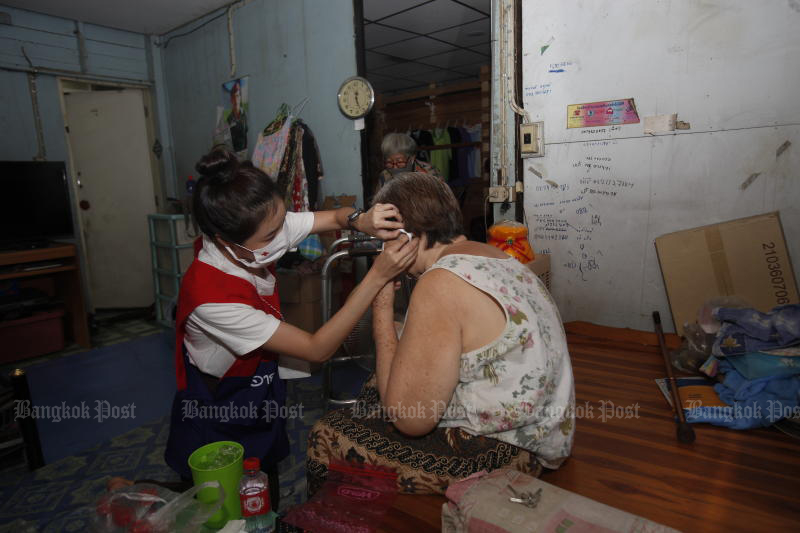 A Red Cross volunteer shows a woman how to properly put on a face mask, during a health campaign in a community near Wat Makok in Phaya Thai district on Saturday. (Photo:  Nutthawat Wicheanbut)