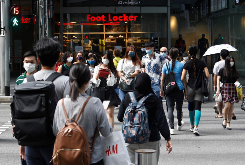 Shoppers wearing protective face masks cross Orchard Road in Singapore on Aug 17, 2020. (Reuters photo)