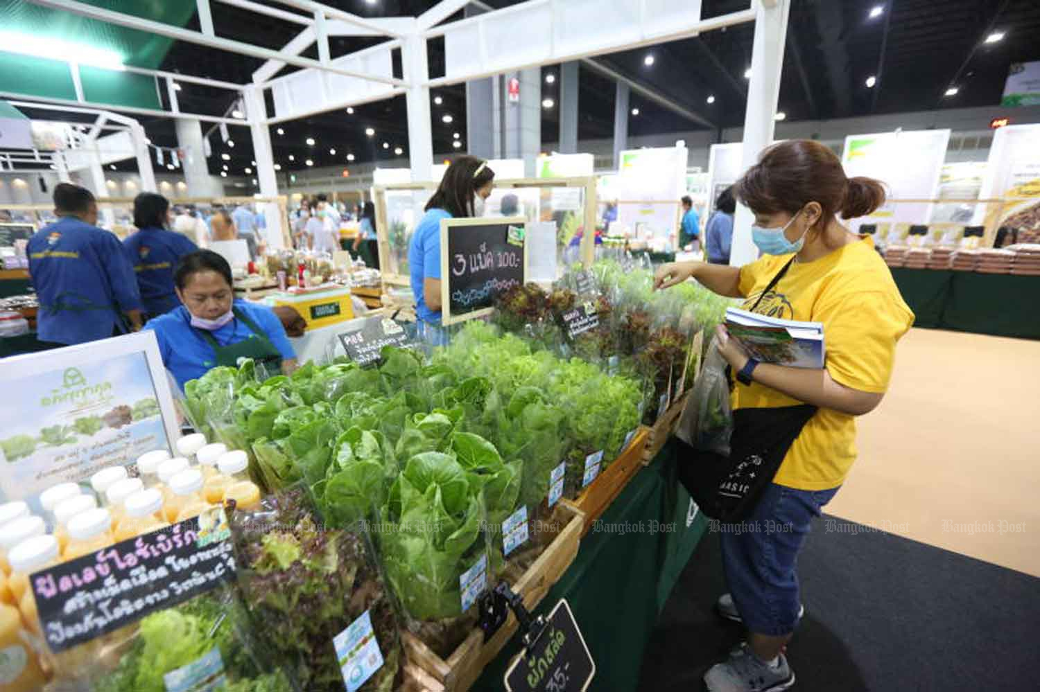 Visitors and vendors wear face masks to help prevent the spread of Covid-19 at a farm product fair in Nonthaburi province on Thursday. (Photo: Pattarapong Chatpattarasill)