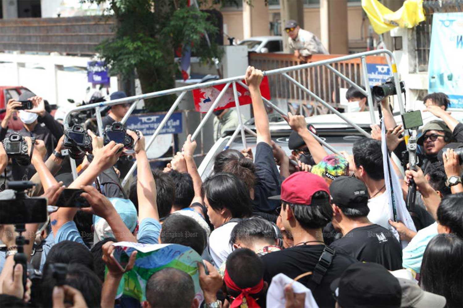 Supporters of pro-democracy activists remove police barricades in front of Samran Rat police station in Bangkok, as 15 activists arrive to acknowledge charges against them in connection with a rally on July 18. (Photo by Apichart Jinakul)