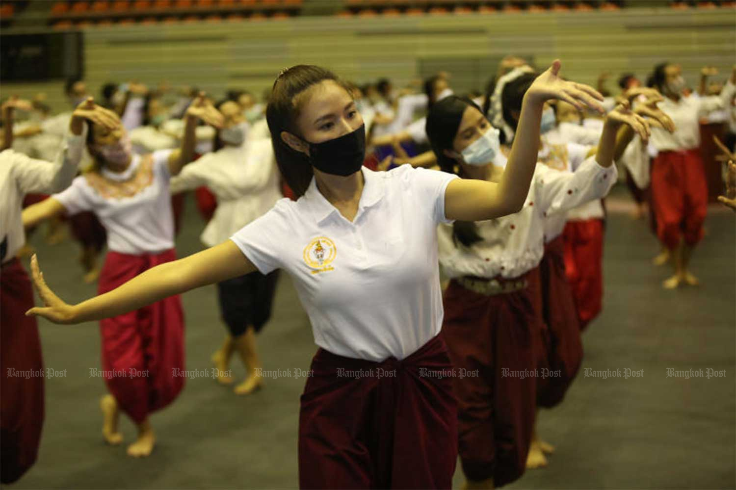 Young women wearing face masks perform a traditional Thai dance show in an annual ceremony to pay respects to those who transferred dancing knowledge to dancers. The ceremony, organised by the Bangkok Metropolitan Administration, was held at the Thai-Japanese Stadium on Aug 27. (Photo: Varuth Hirunyatheb)