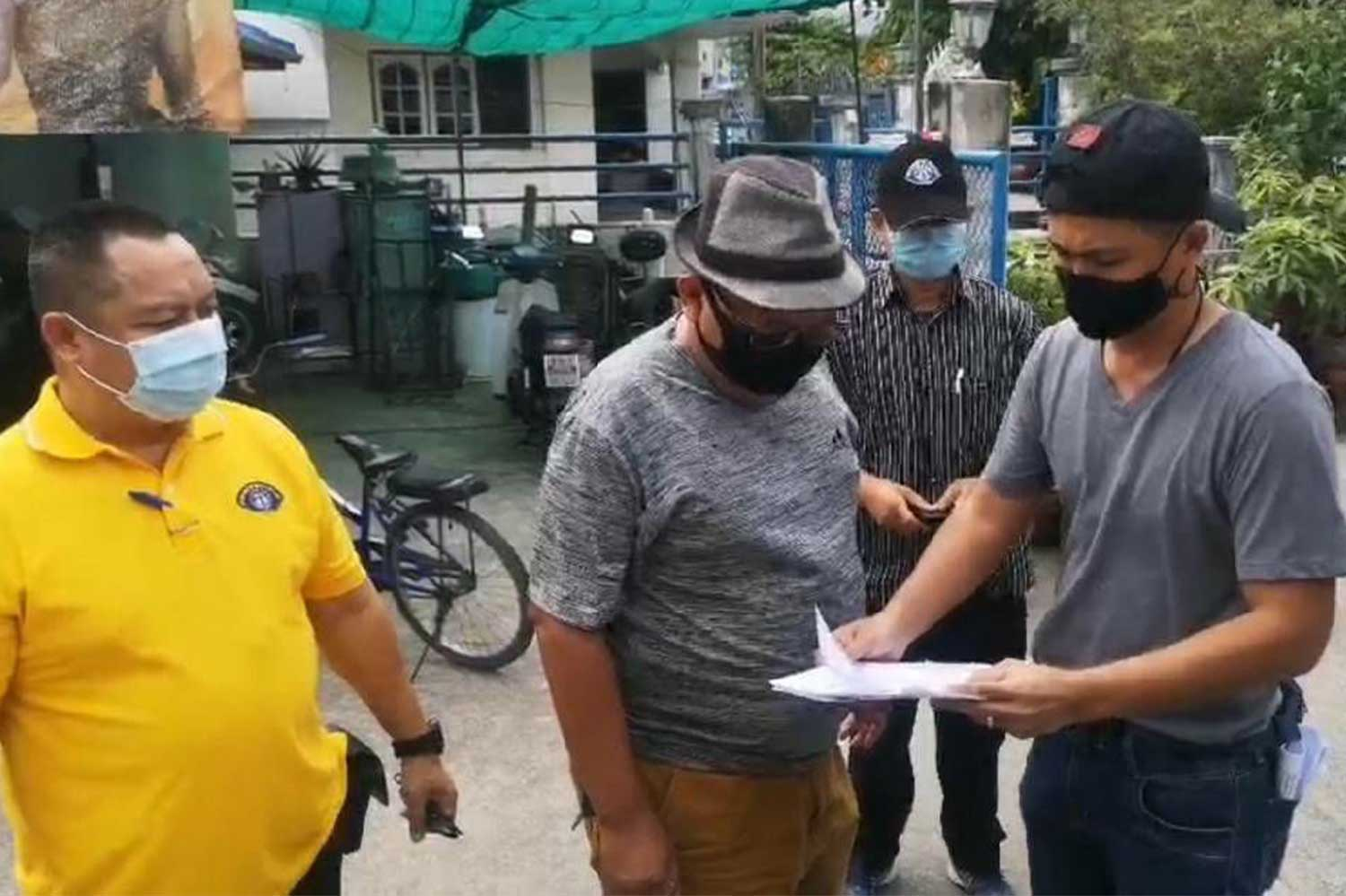 Plainclothes police show an arrest warrant to a 56-year-old man (centre) before taking him into custody in Pak Kret district of Nonthaburi on Friday. (Photo: Crime Suppression Division)