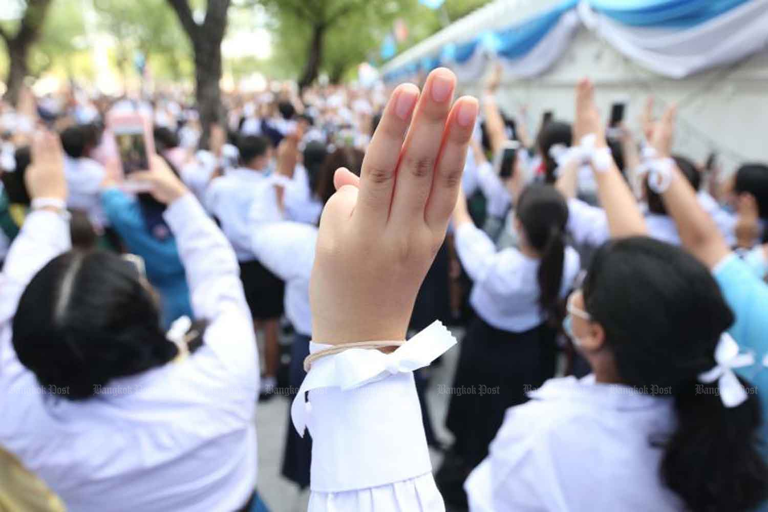 Students give the three-finger salute during a rally at the Education Ministry in Bangkok on Aug 19. (Photo: Pattarapong Chatpattarasill)