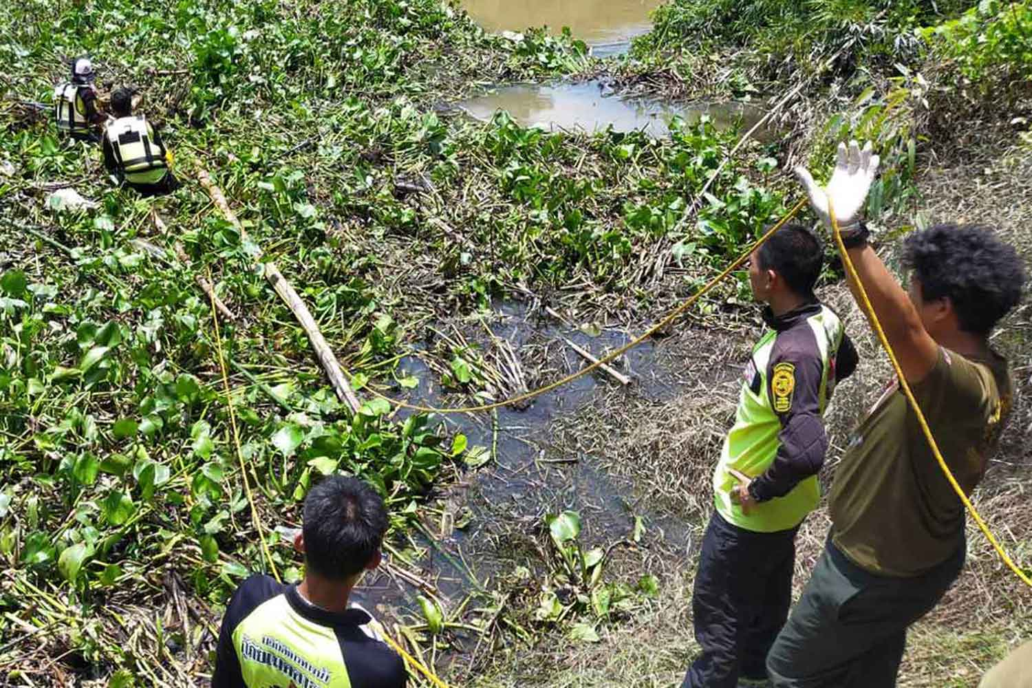 Rescuers retrieve the body of an elderly woman from Lam Pao stream in Muang district, Kalasin, on Sunday. The woman disappeared into the water on Friday. (Photo: Yongyuth Phuphuangpet)