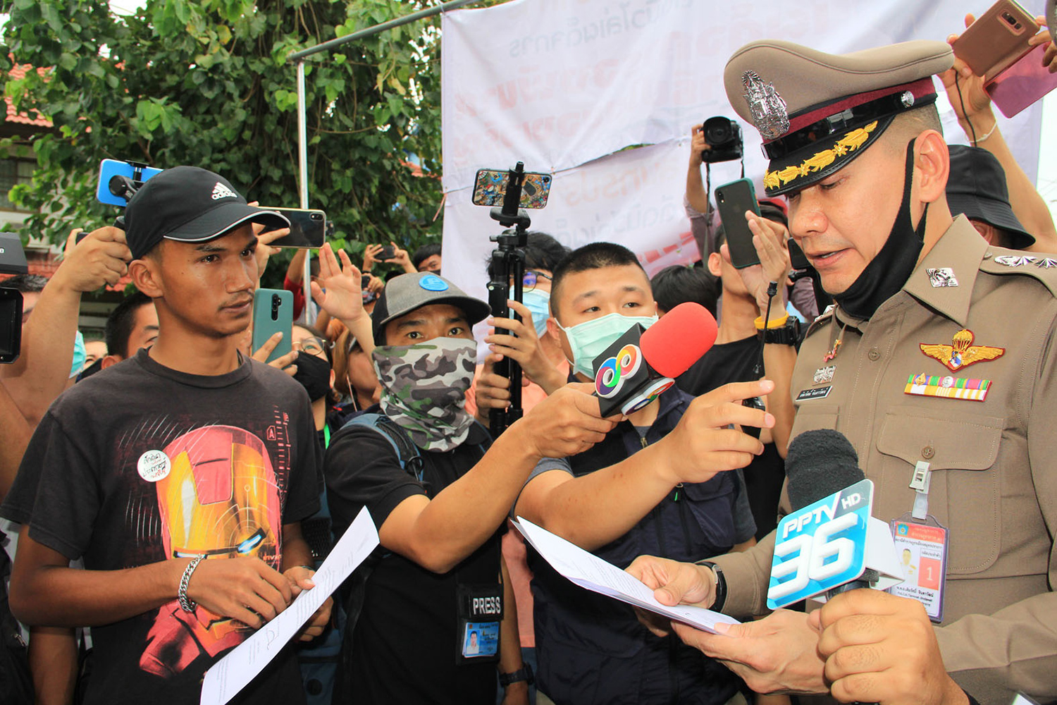 Activist Panupong Chadnok receives a copy of the Public Assembly Act from Pol Col Termras Jindawat, the Muang police station chief, during the rally in Muang district of Samut Prakan on Sunday.