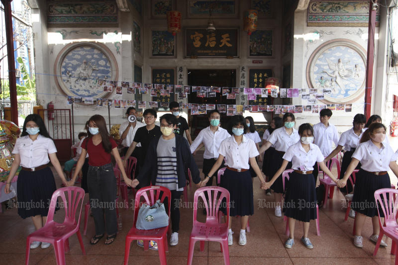Students join hands on Monday in a bid to protect the Chao Mae Thap Thim shrine from demolition. (Photo by Arnun Chonmahatrakool)