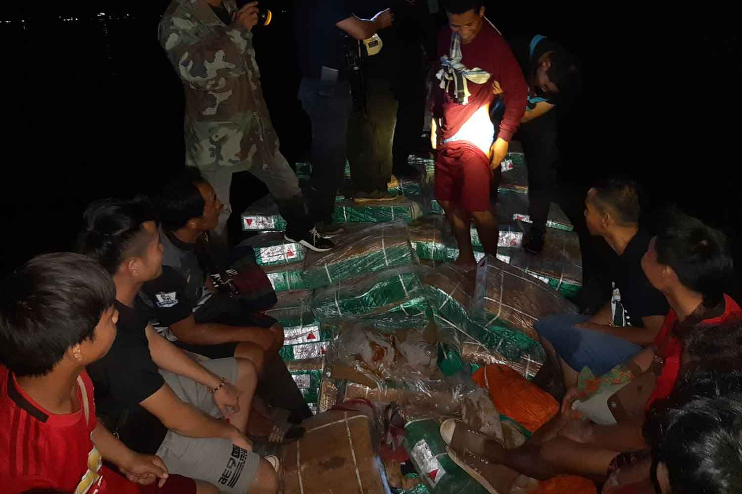Rangers examine packs of beef smuggled across the Mekong river from Laos to Mukdahan on Monday night. Nine Lao smugglers were arrested.(Photo: Churoj Triprapakorn)