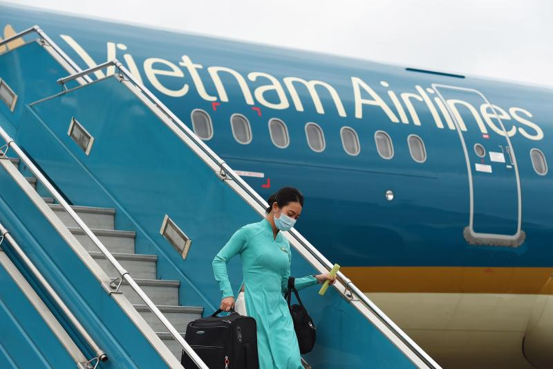 In this file photo taken on March 3, 2020 a Vietnam Airlines flight crew member wearing a facemask amid concerns of the spread of the Covid-19 coronavirus disembarks from a flight returning from Taiwan at Noi Bai International Airport in Hanoi.