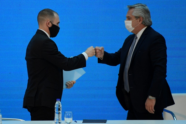 Argentina's President Alberto Fernandez (R) and Economy Minister Martin Guzman greet each other with a fist bump after announcing the restructuring of a $66 billion foreign-law debt