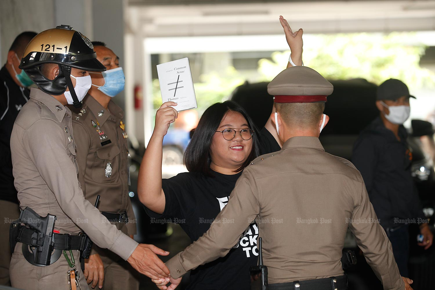 Jutatip Sirikhan, 21, the president of the Student Union of Thailand, holds a book titled 'Common Sense' at Samranrat police station in Bangkok's Phra Nakhon district following her arrest in connection with the July 18 anti-government protest. (Photo by Nutthawat Wicheanbut)