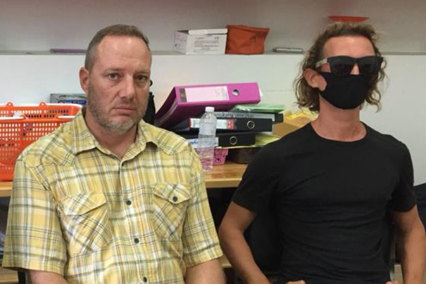 Attila Ott (left) and Francesco Simonetti report to police on Koh Phangan on Tuesday on charges of intruding in an area designated for environmental protection. (Photo: Supapong Chaolan)