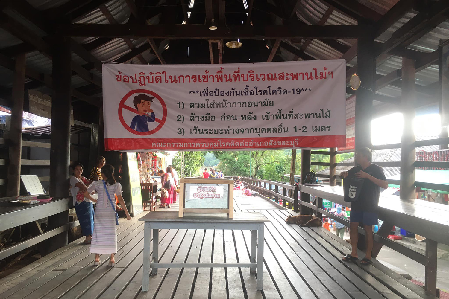 A banner reminds residents and visitors not to lower their guard against Covid-19 at the famous Mon Bridge in Sangkhla Buri district of Kanchanaburi. (Photo: Piyarach Chongcharoen)