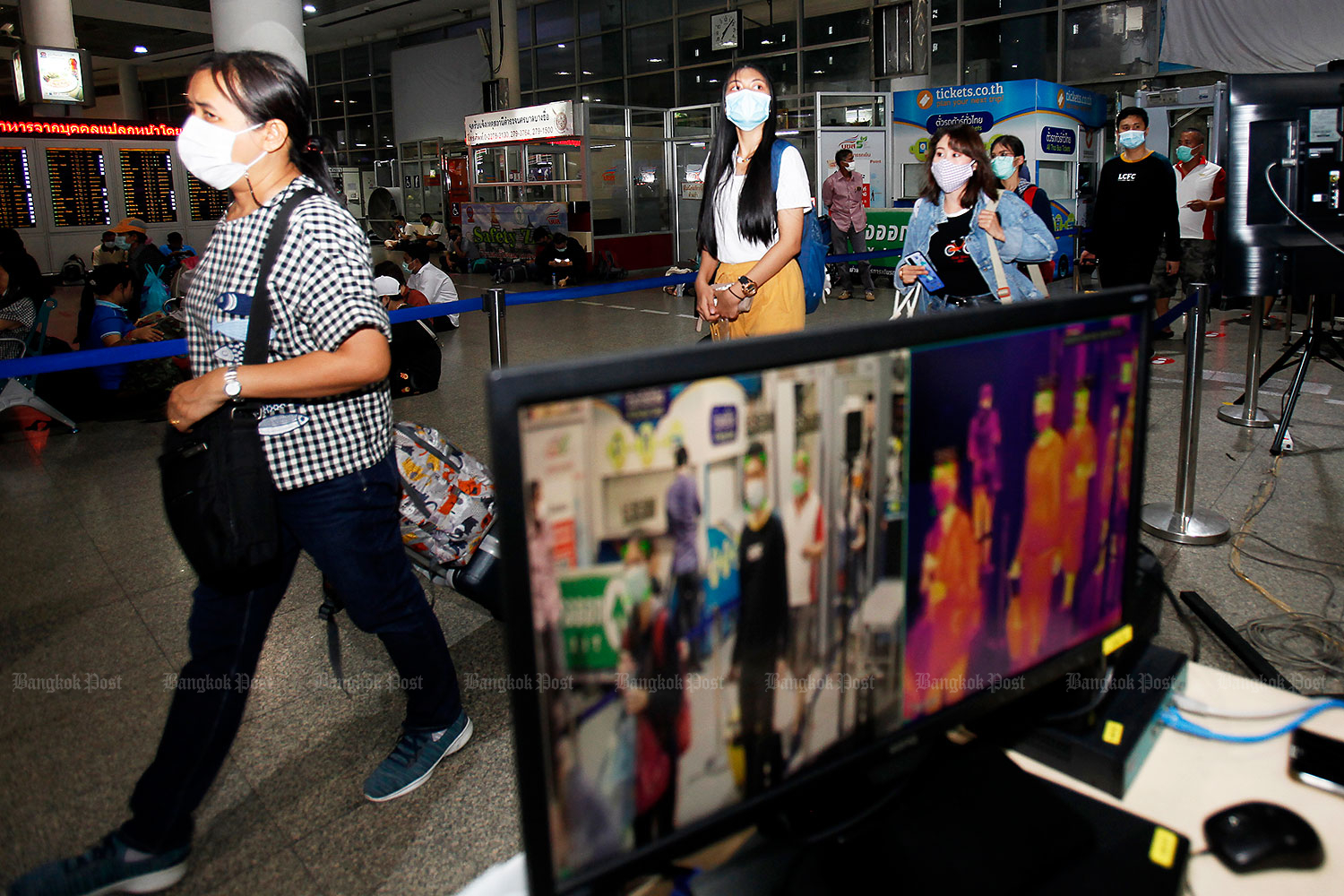 On the lookout: People walk past a thermal scanner as they make their way into the terminal at the Mor Chit bus depot in angkok yesterday. The state-owned Transport Company announced it was putting more inter-provincial buses into service during the long weekend to cope with the exodus of holidaymakers. (Photo by Nutthawat Wicheanbut)