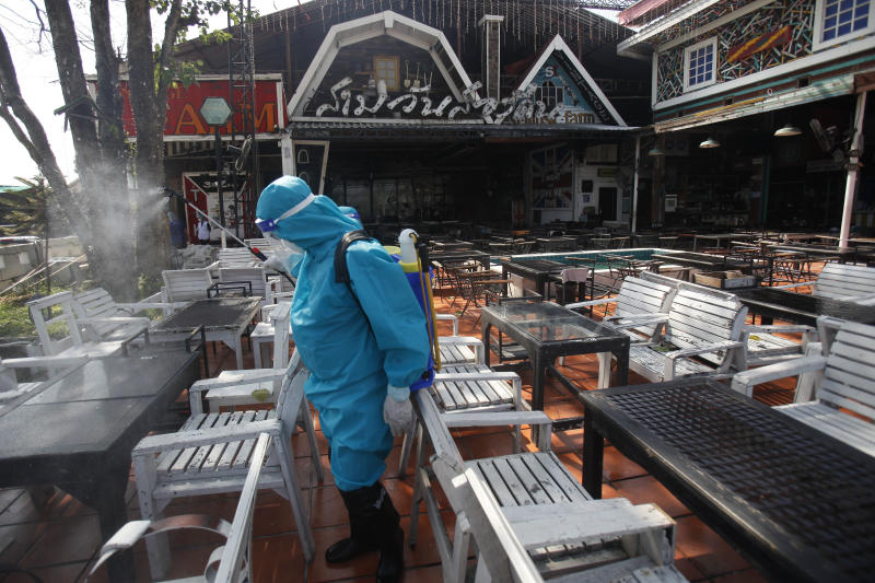 A sanitation worker sprays disinfectant at the 3 Day 2 Night pub on Rama V Road in Nonthaburi on Friday. (Photo by Nutthawat Wicheanbut)