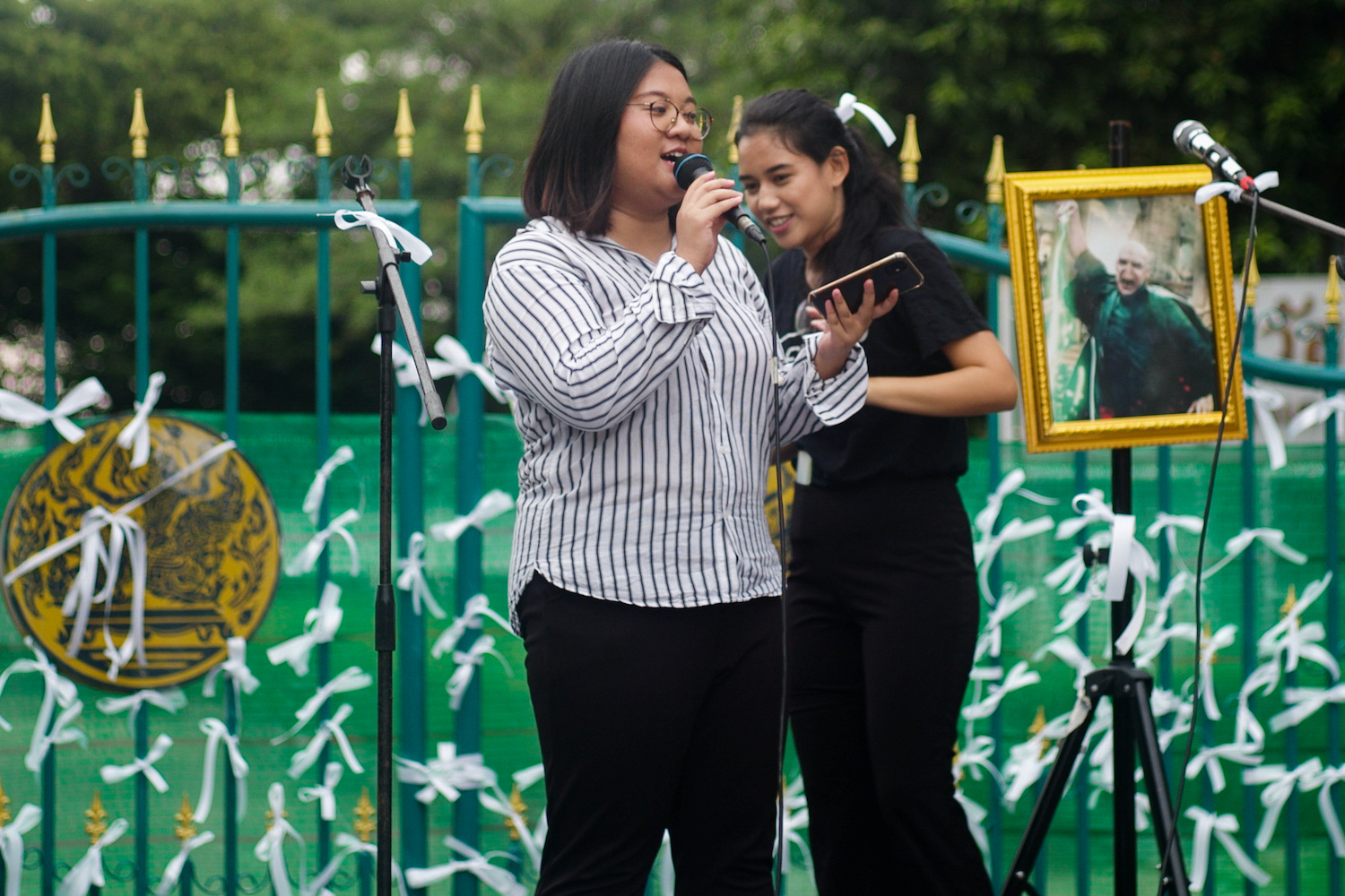 Jutatip Sirikhan, president of the Student Union of Thailand, speaks in front of the ribbon-bedecked gate of the gate of Bangkok Remand Prison to call for the release of activists Anon Nampa and Panupong Jadnok on Friday. (Reuters Photo)