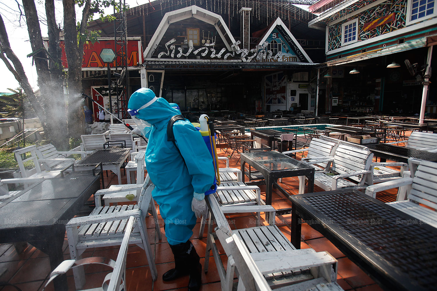 A worker sprays disinfectant at the Sam Wan Song Khuen pub on Rama V Road in Nonthaburi. The pub is to remain closed until tomorrow. The latest Covid-19 patient worked as a DJ at the premises on Fridays and Sundays. (Photos by Nutthawat Wicheanbut)