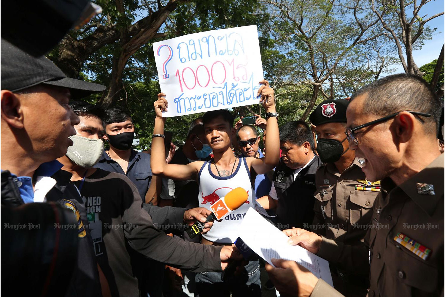 In this Aug 24 photo, activist Panupong 'Mike' Jadnok holds up a placard as he rallies against a huge sea reclamation project in Rayong shortly before Prime Minister Prayut Chan-o-cha's arrival in the province.(Photo by Pattarapong Chatpattarasill)