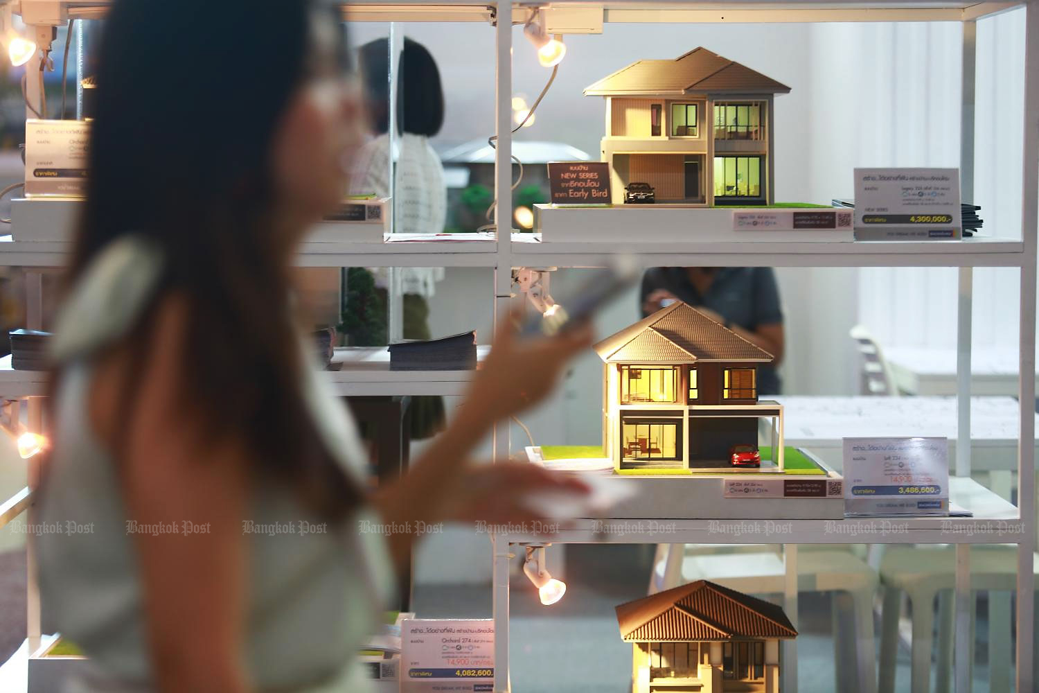 A woman passes model houses at last year's House and Condo Expo. The central bank says recent housing loan applications represent real demand.