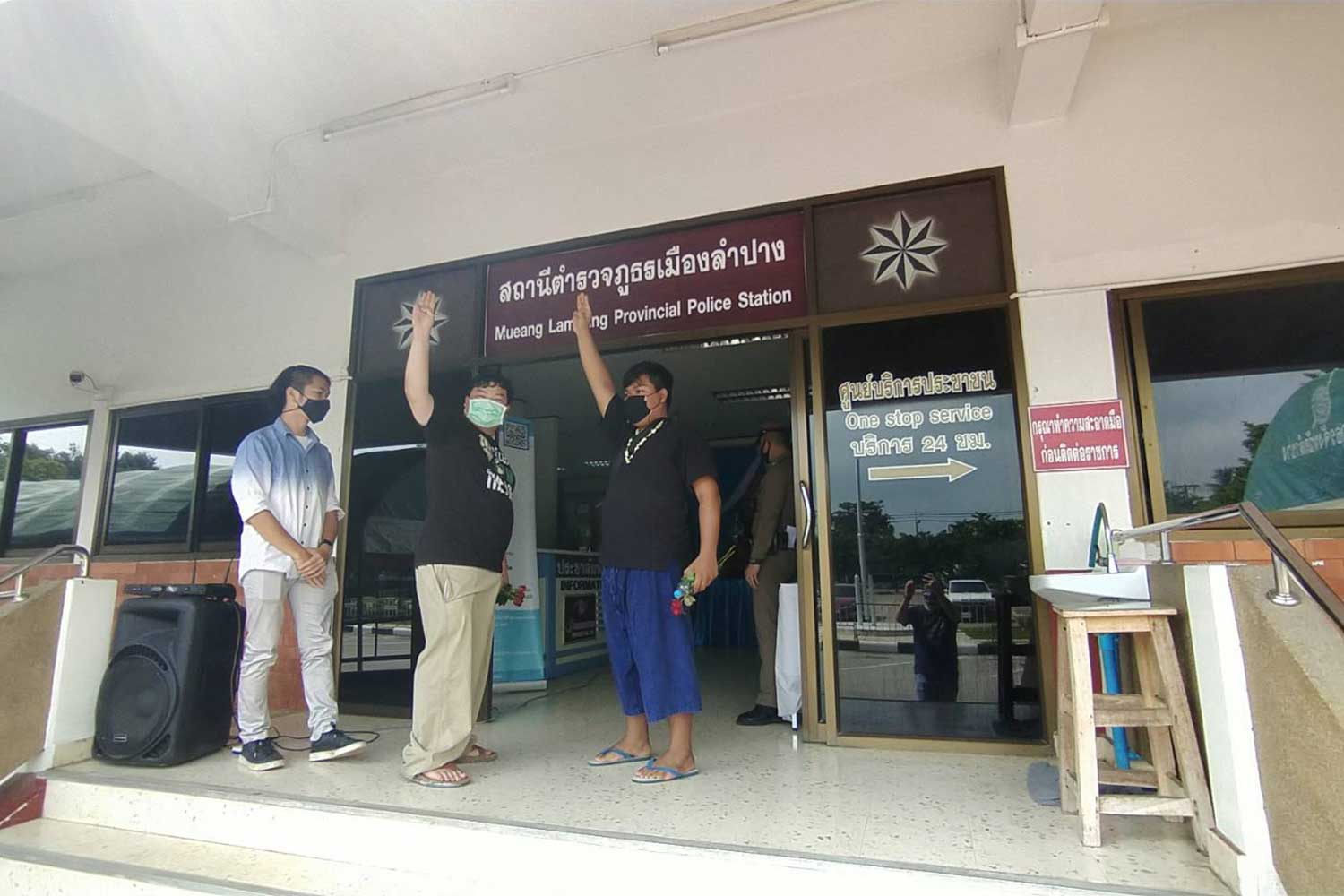 """Parit """"Penguin"""" Chiwarak (centre) gives a three-finger salute outside the Muang district police station on Saturday, where he and two colleagues heard charges related to a July 26 rally in Lampang. (Photo by Assawin Wongnorkaew)"""