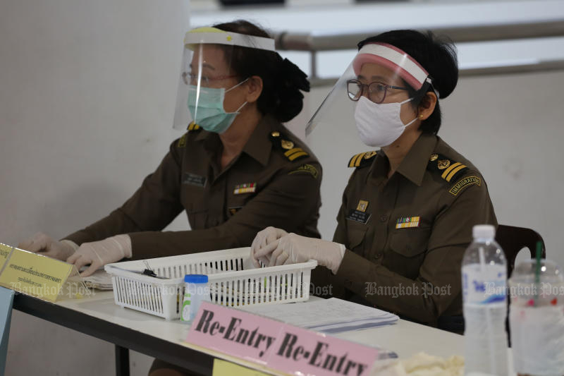 Immigration authorities work at the Immigration Bureau office at the Government Complex on March 24, 2020. (Photo by Varuth Hirunyatheb)