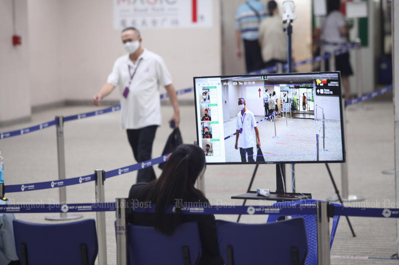 A traveller passes through a body temperature scanner at Don Mueang airport on Thursday. Thailand added six new coronavirus cases on Sunday. (Photo by Arnun Chonmahatrakool)