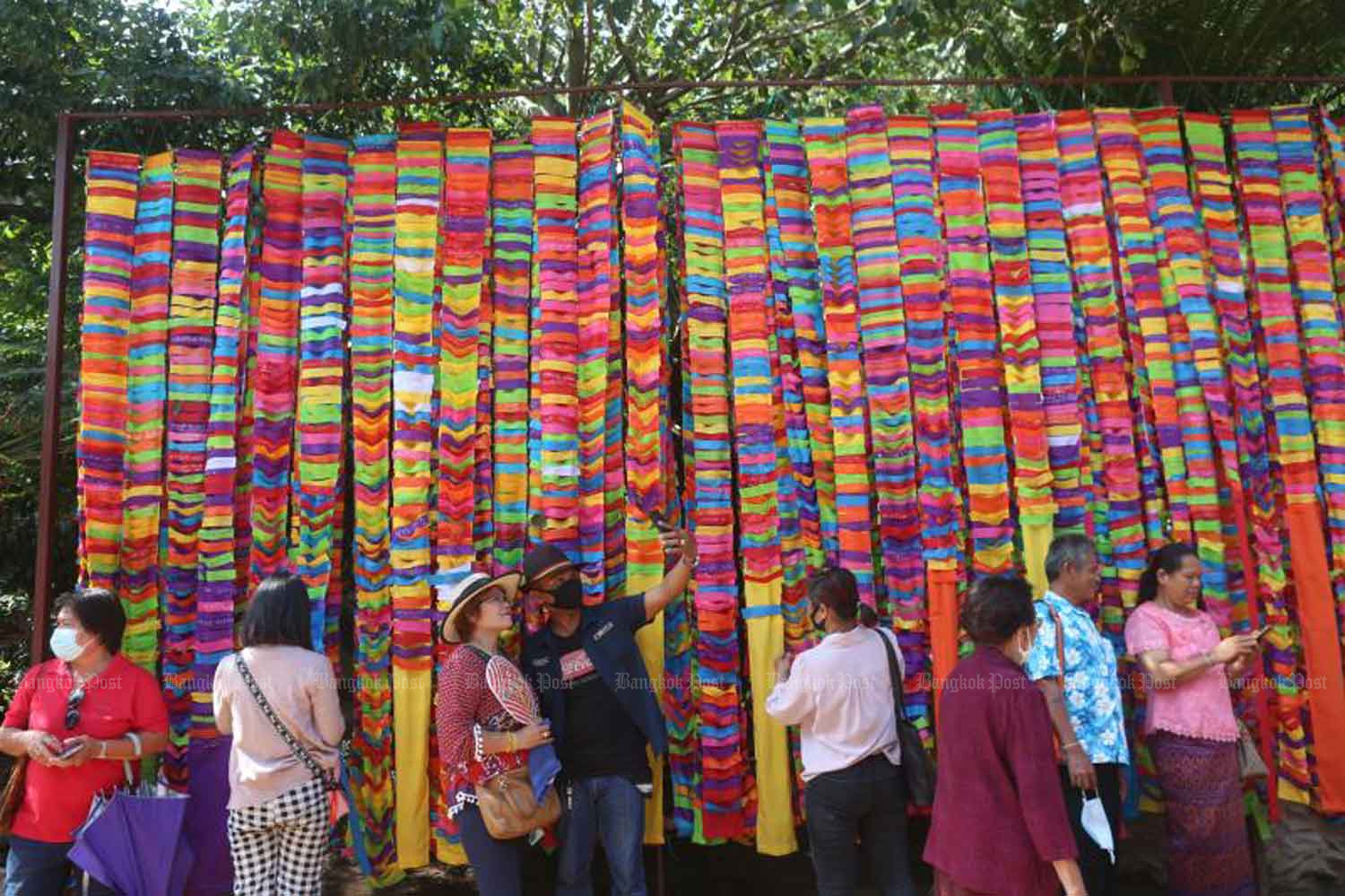 Tourists use brightly-coloured cloths in a merit-making rite at Wat Tham Pha Daeng, a temple on Phu Phan mountain range in Sakon Nakhon's Muang district, during the long weekend. The temple is well-known for its sandstone reliefs. PATTARAPONG CHATPATTARASILL