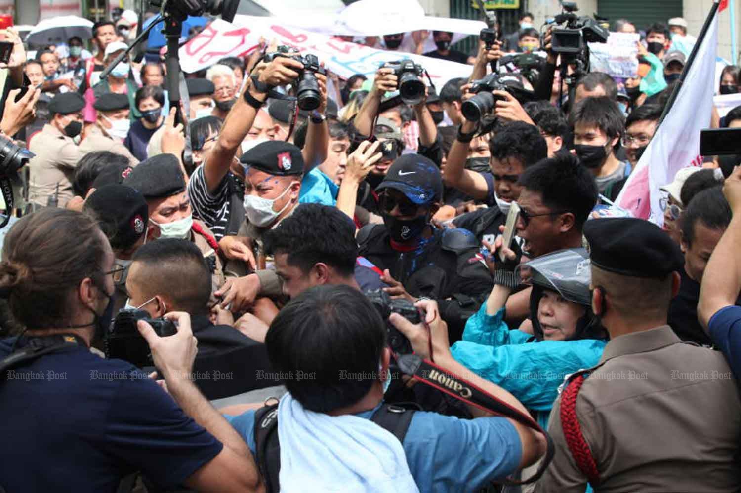 Anti-government protesters scuffle with police as they try to break barriers and storm inside Samran Rat police station in Bangkok where 15 political activists arrived on Aug 28 to acknowledge charges against them in connection with a rally on July 18. Blue paint in bags and a bucket was thrown at the officers during the ruckus. (Photo by Apichart Jinakul)