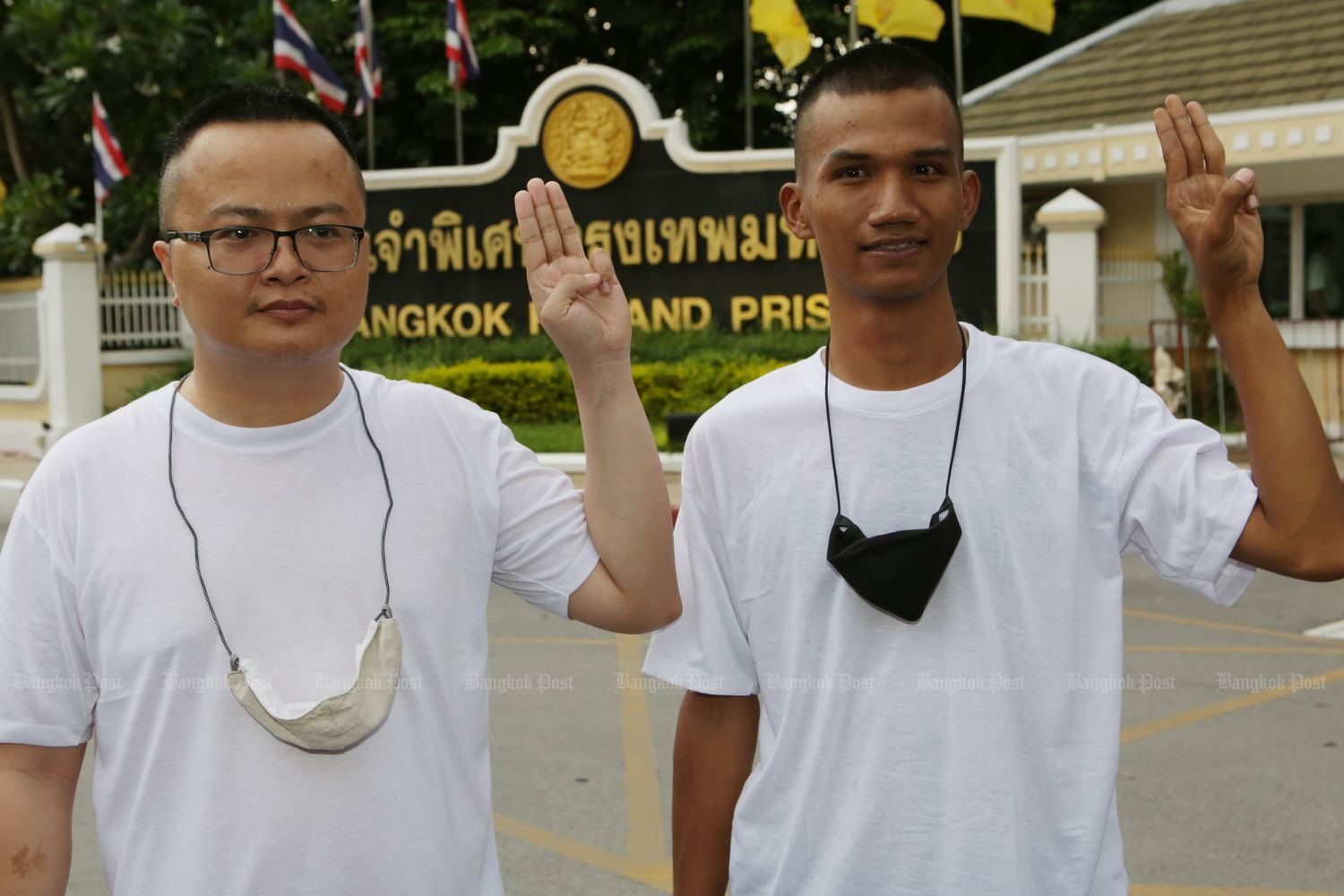 Lawyer Anon Nampa (left) and student activist Panupong 'Mike' Jadnok shows a symbol of their pro-democracy protest after being released from Bangkok REmand Prison in Bangkok on Monday evening. (Photo by Apichit Jinakul)