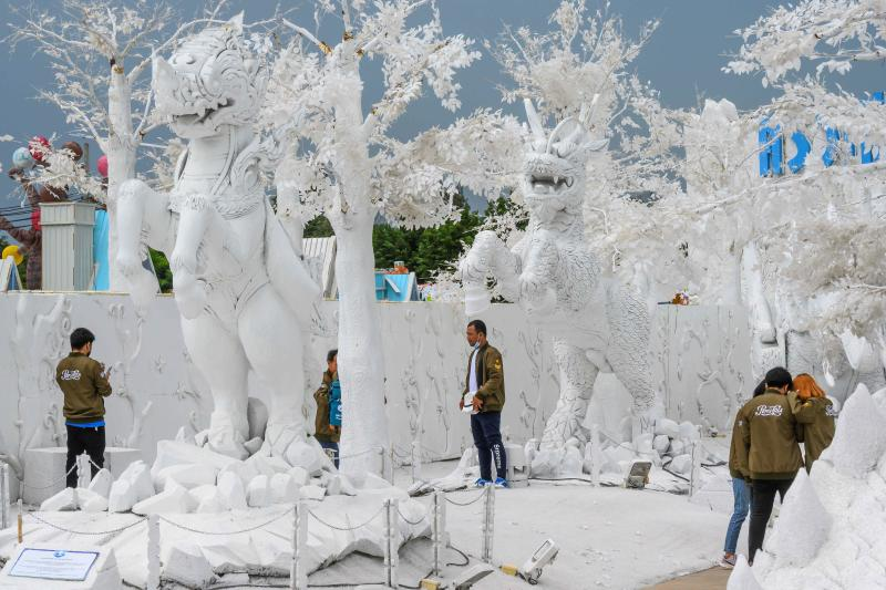 Visitors take pictures in front of sculptures made of white sand imitating ice in the