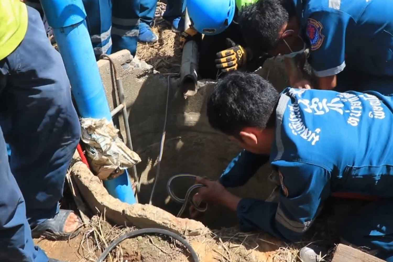 Rescuers drop a rope down the well to bring up the two unconscious men, father and  son, in Phitsanulok on Wednesday. The two men died. Neighbours believed they inhaled hydrogen sulfide. (Photo: Chinnawat Singha)