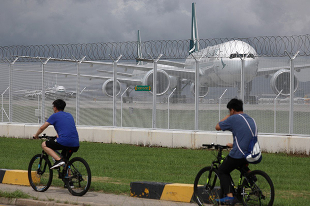 Two cyclists pass a line of grounded Cathay Pacific aircraft at Hong Kong International Airport. (South China Morning Post photo)